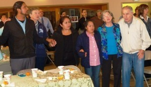 Participants in the Labor Seder conducted by the Interfaith Center for Worker Justice in Kensington on April 4 rise to sing during the ceremonial Passover meal. (Photo by B.J. Coleman)