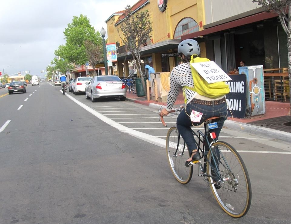 "A cyclist donning the ""SD Bike Train"" sign rides along University Avenue. (Photo by Veronica Medina)"