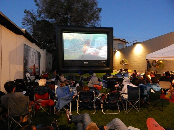 "Local residents gather last year for ""Hillcrest Movie Night in the Egyptian Quarter."" An outdoor screen is set up in the parking lot turned pop-up park between Heat Bar & Kitchen and the Numbers Nightclub. (Courtesy of Hillcrest Business Association)"