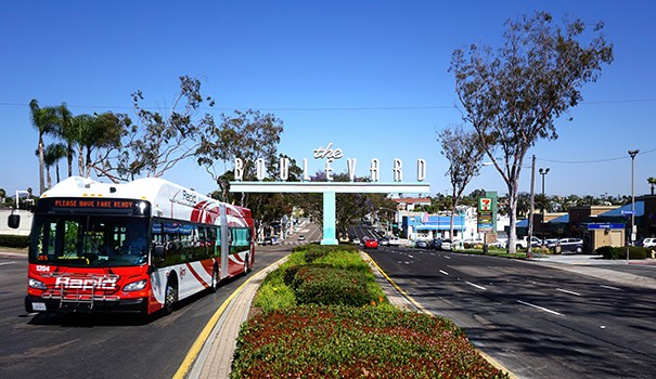 Mid-City Rapid Bus 215 runs past the iconic The Boulevard sign. (Courtesy of El Cajon Boulevard Business Improvement Association)