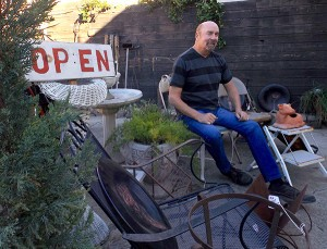 Scott Harring sits on his store's back yard
