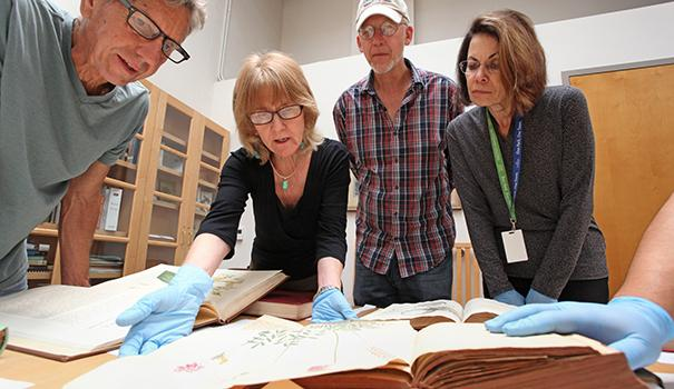 Exhibits team members examine rare book illustrations in the Research Library ahead of construction. Margi Dykens (second from left) is the longtime director of the Research Library. (Courtesy of the NAT)