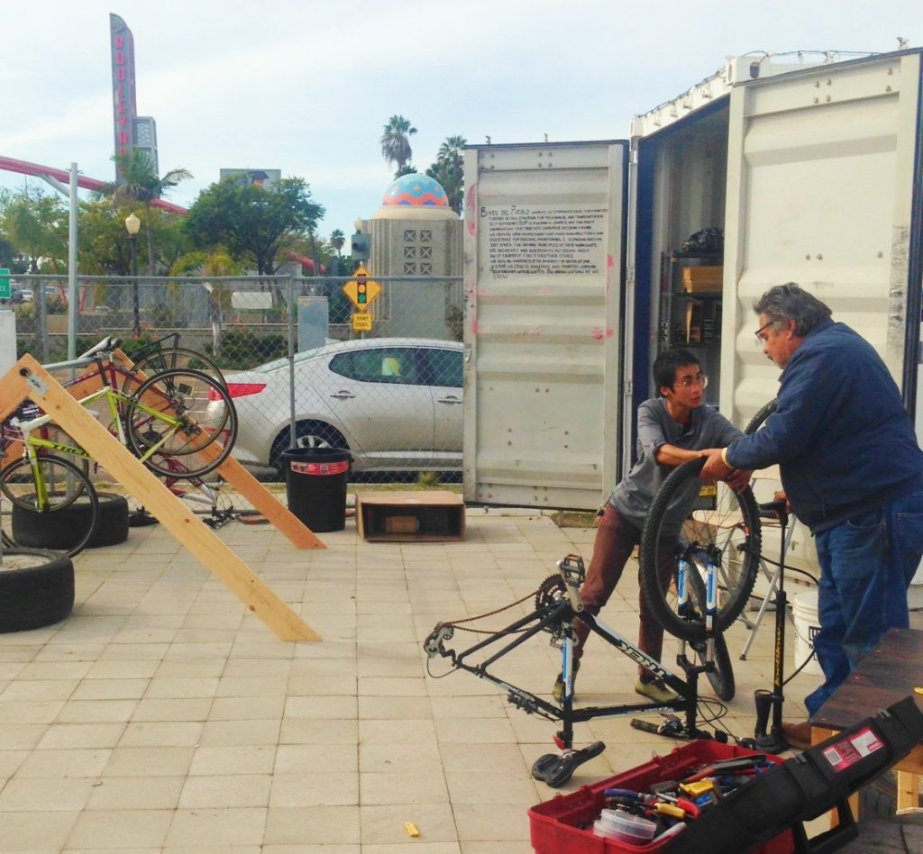 Val, with Bikes del Pueblo, repairs a customer's bike. (Courtesy of El Cajon Boulevard Business Improvement Association)