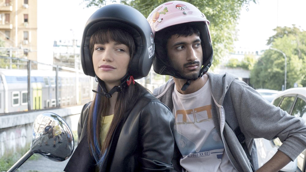 A young couple wearing bike helmets. The man and woman are looking to the side.